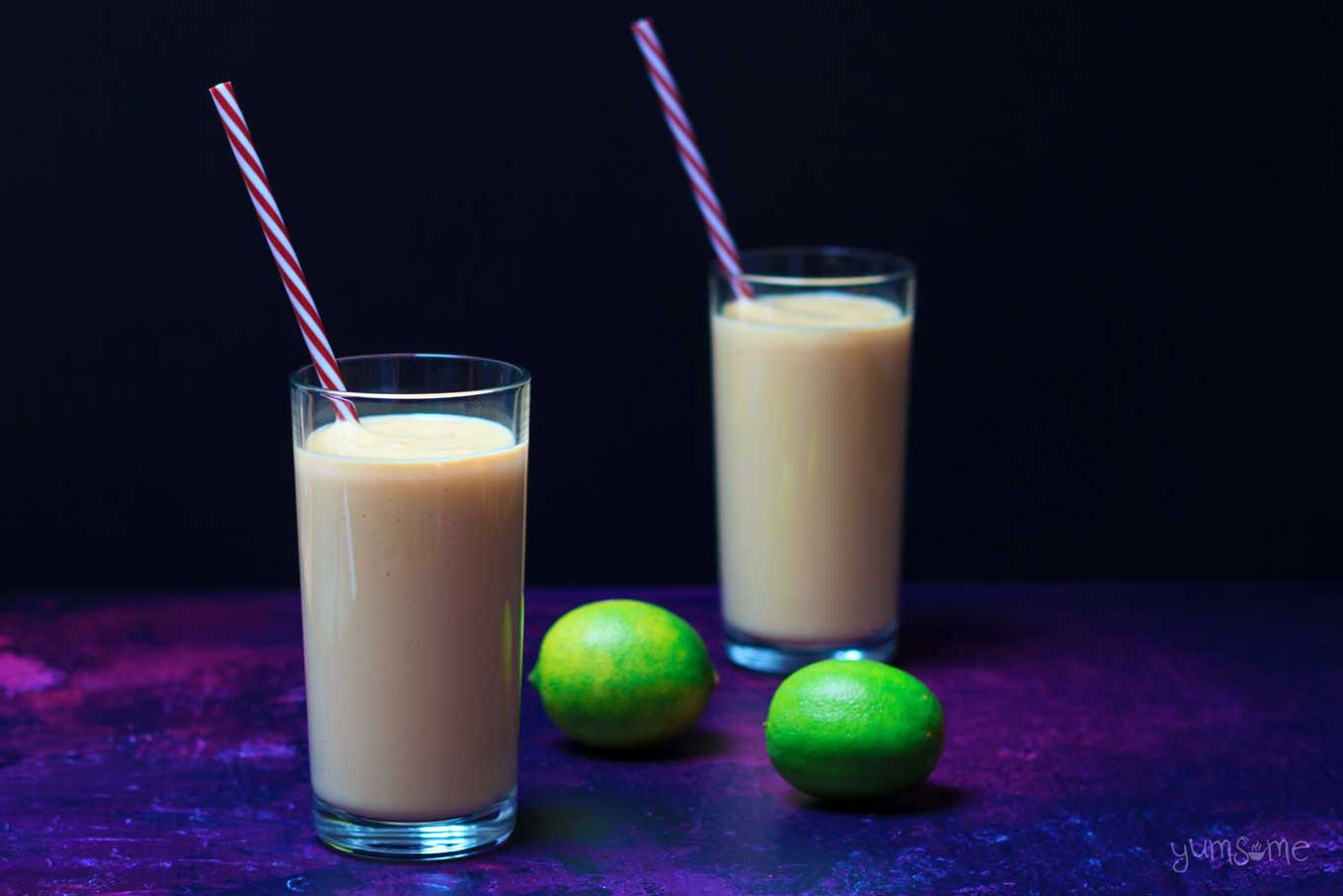 two glasses of quick and easy vegan mango and lime lassi with two limes | yumsome.com
