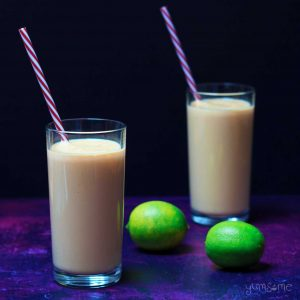 Two limes and two glasses of vegan mango lassi.