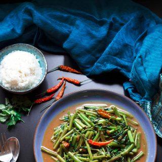 Overhead shot of a plate of vegan vegan Thai stir-fried morning glory.