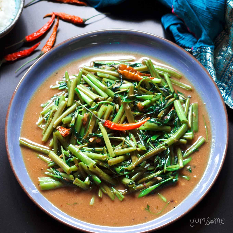 Thai stir-fried morning glory on a blue plate.