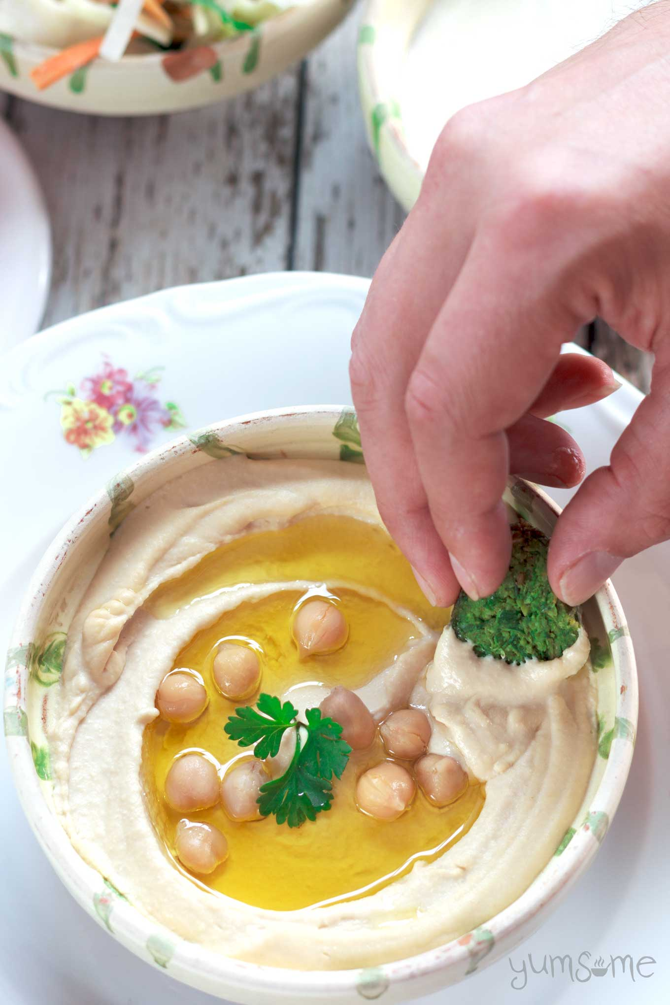 falafel dipped into a bowl of perfectly smooth and creamy hummus | yumsome.com