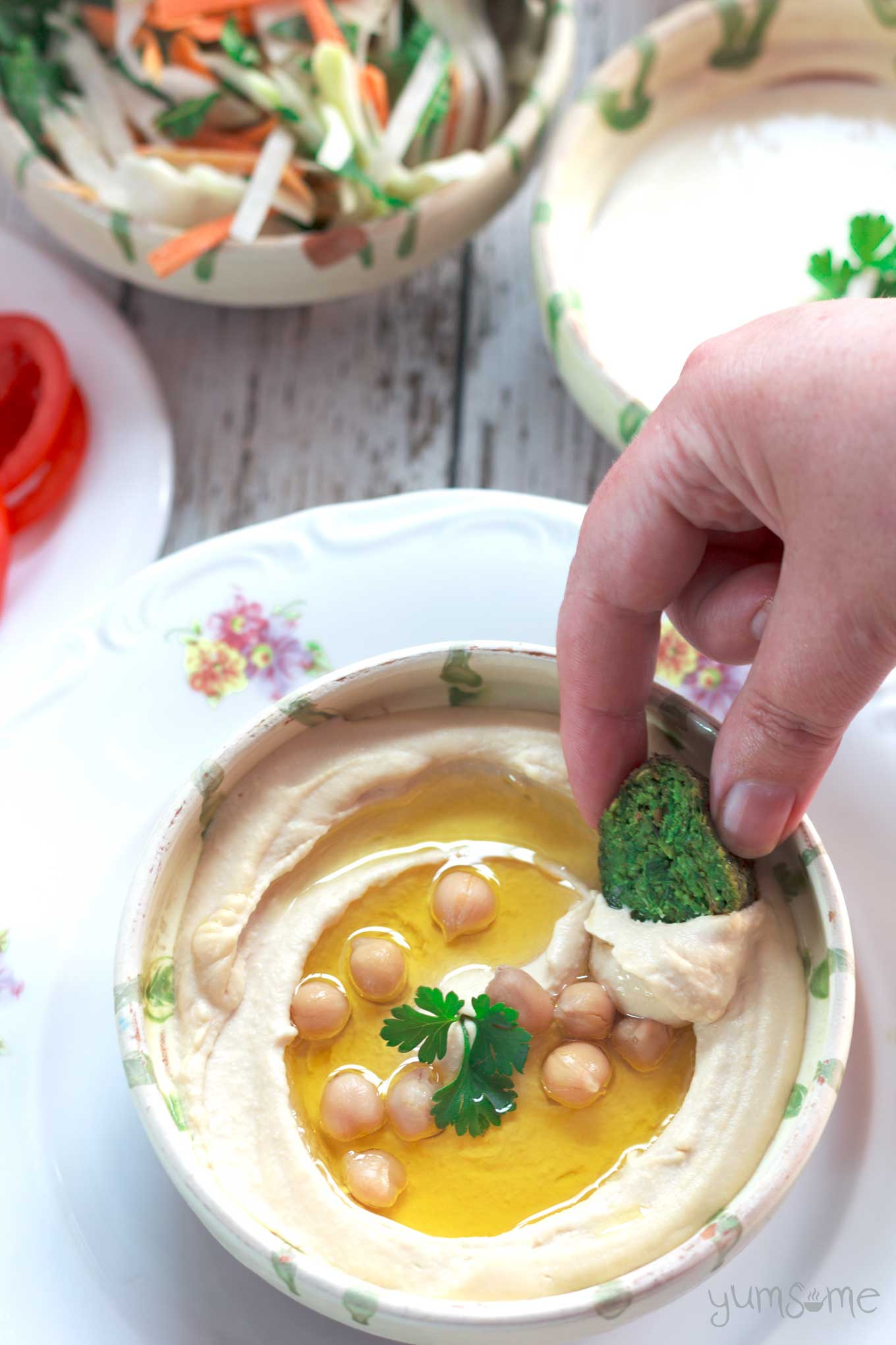 A hand dipping falafel into perfectly smooth and creamy hummus.