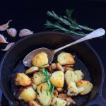 roast potatoes in a skillet with a serving spoon, some rosemary, and a few cloves of garlic   yumsome.com