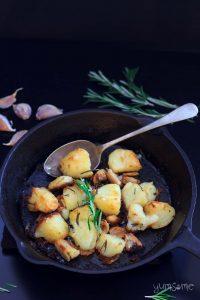 roast potatoes in a skillet with a serving spoon, some rosemary, and a few cloves of garlic | yumsome.com
