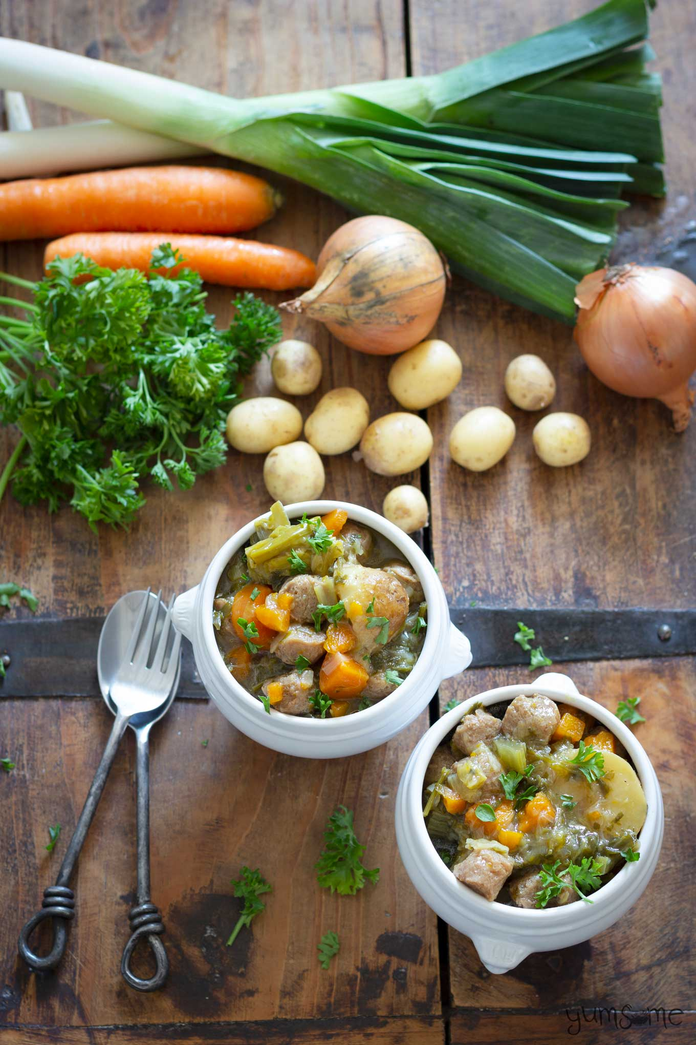 Overhead photo of two bowls of simple vegan Irish stew and some vegetables.