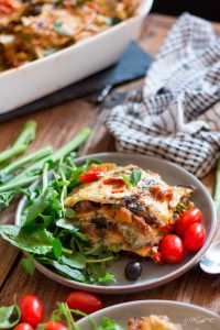 loaded vegan lasagne on a plate, plus green salad leaves and baby plum tomatoes | yumsome.com