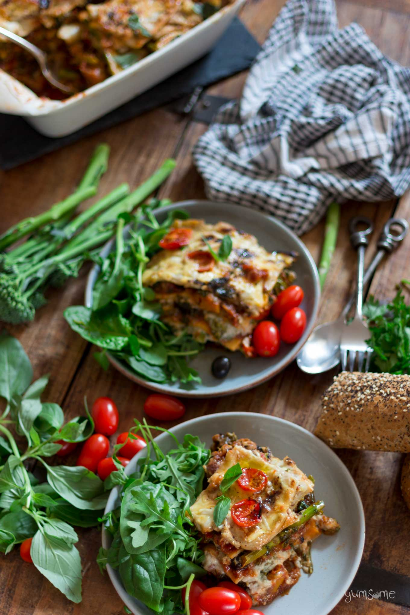 overhead shot of two plates of loaded vegan lasagne with green salad, baby plum tomatoes, tenderstem broccoli, basil, and some bread | yumsome.com