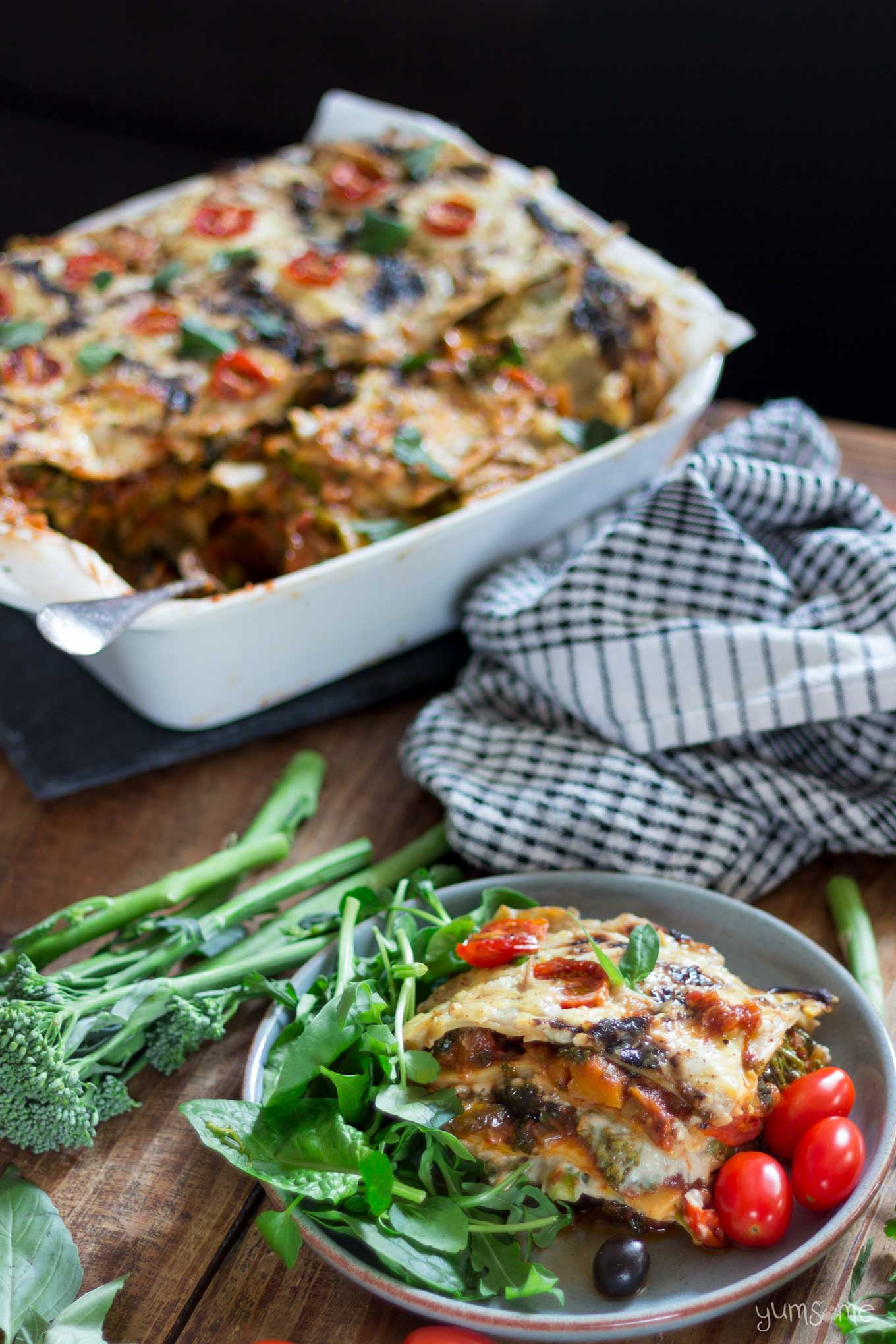 a large dish, plus a plate of loaded vegan lasagne, with green salad and tomatoes, plus a tea towel | yumsome.com