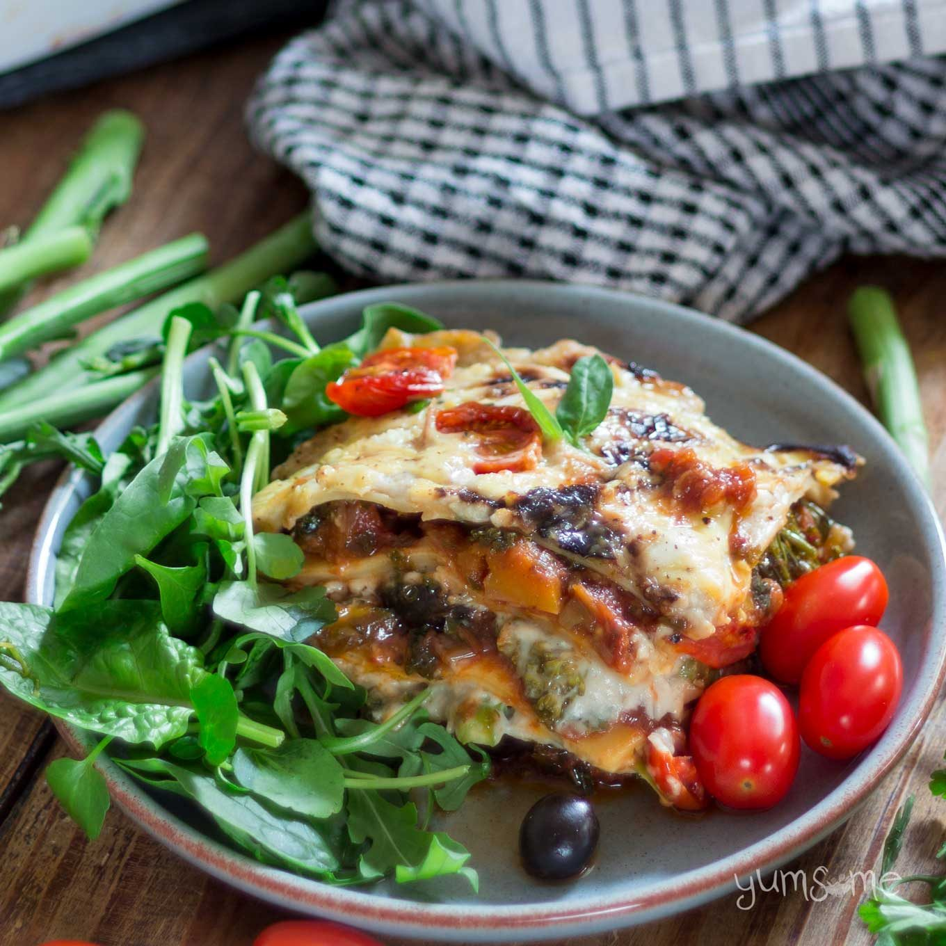 a plate of loaded vegan lasagne, with green salad and tomatoes, plus a tea towel | yumsome.com