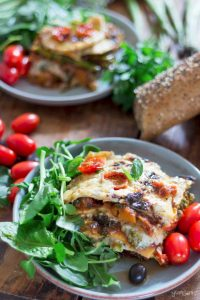 Two plates of loaded vegan lasagne, with green salad and tomatoe.
