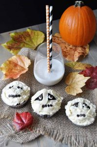 A Halloween table with mummy-shaped cupcakes, a pumpkin, and a glass of milk, surrounded by autumn leaves.