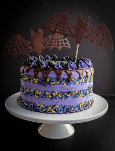 A large purple cake, adorned with chocolate bats and other Halloween candies.