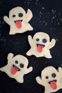 Four sandwiches in the shape of ghost emojis, on a black background.
