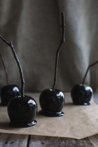 Several black toffee apples on a wooden board.