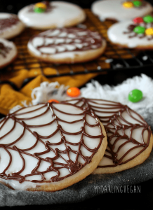 Several cookies decorated with chocolate spider webs, on a table with other vegan candies.