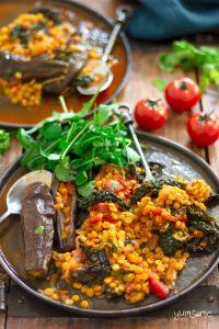 Chana dal, eggplant, and kale casserole on a black plate, and salad.