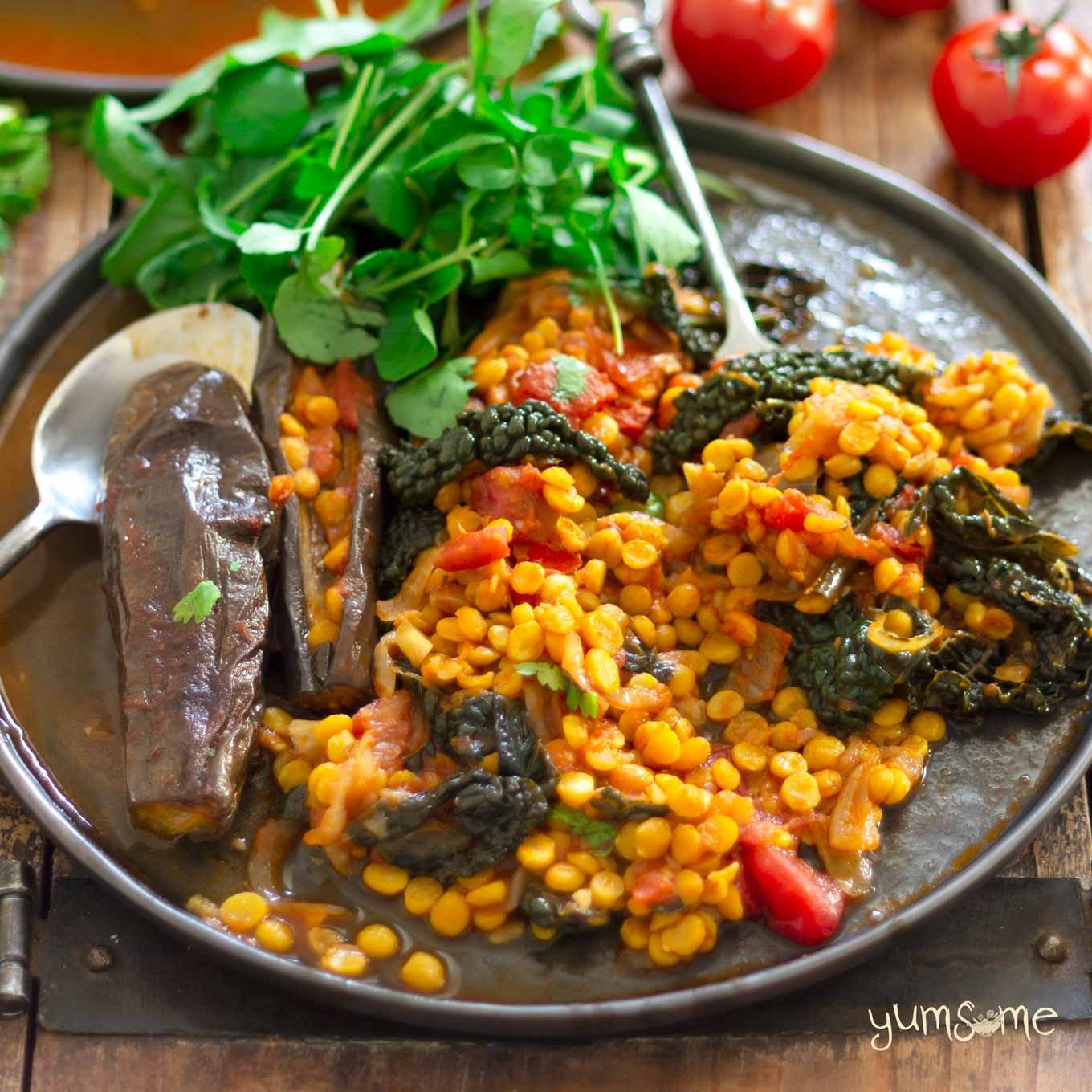 vegan spicy dal, aubergine, and kale casserole on a plate, and salad | yumsome.com
