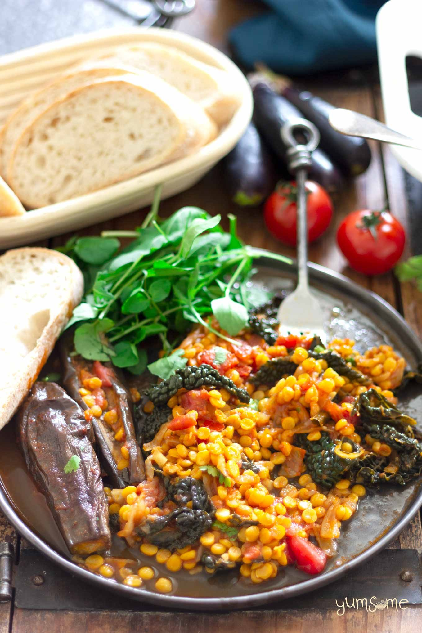 A serving of vegan spicy dal, aubergine, and kale casserole on a plate, with some bread and green salad.