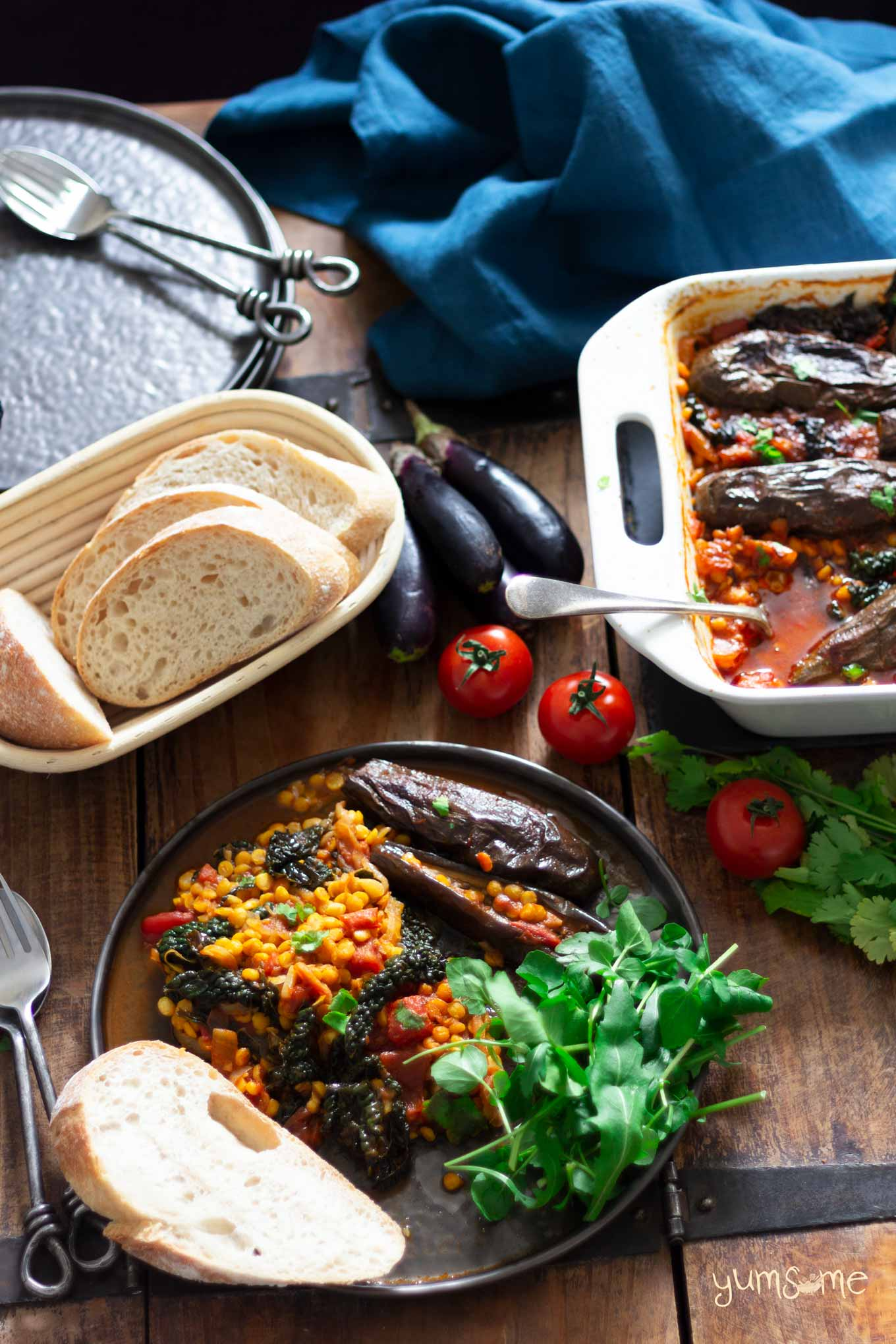 Spicy dal, aubergine, and kale casserole on a plate, plus a basket of sourdough bread.