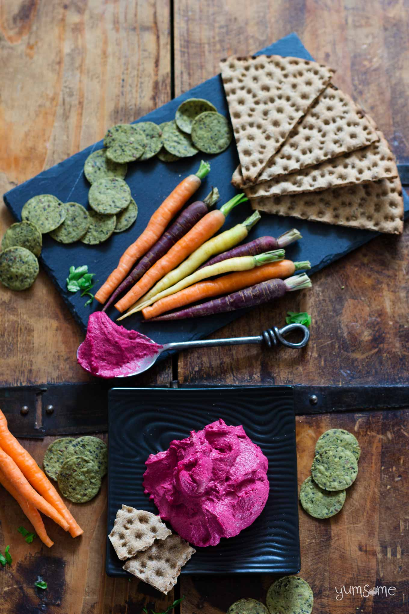 Bright pink beetroot hummus on a black plate, plus multicoloured carrots and crackers.