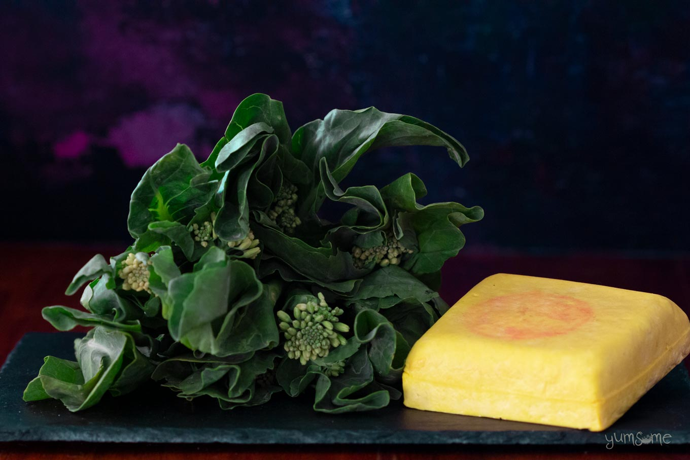 Chinese broccoli and a block of yellow tofu on a dark background.