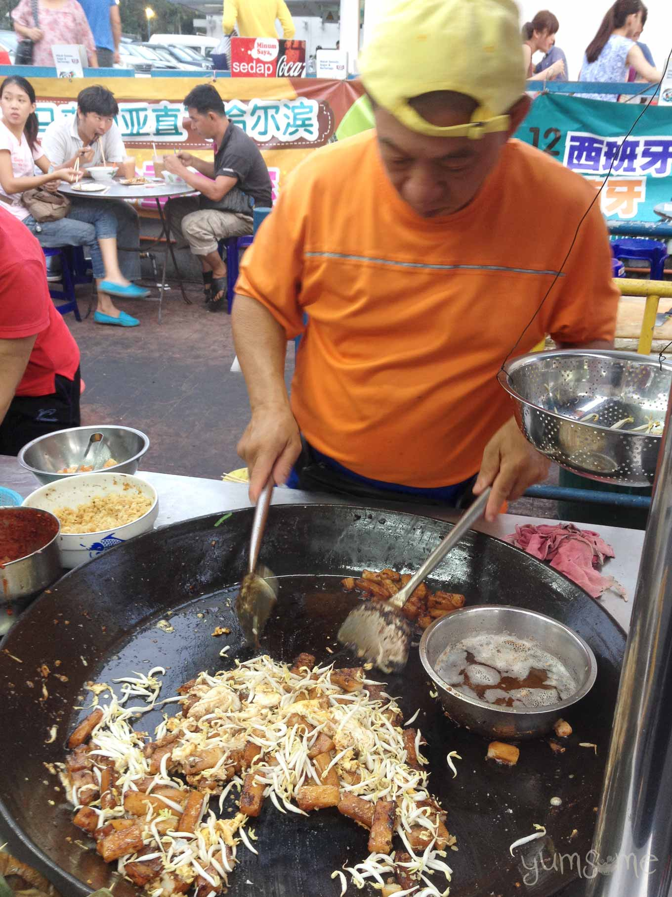 A street hawker in George Town, Penang, making a huge pan of char kway teow (pad see ew). - noodles and tofu fried with soy sauce.