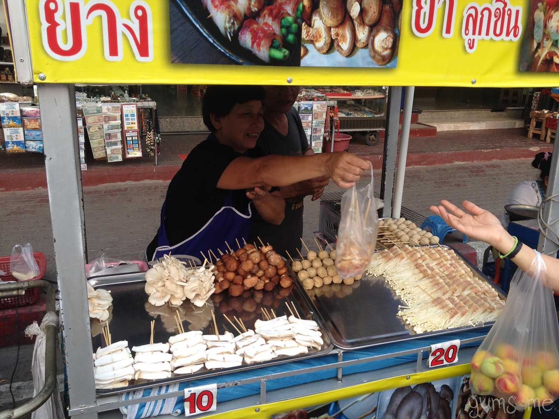 A Thai woman hands over a bag of food at a street food cart in Mae Sai, Thailand.