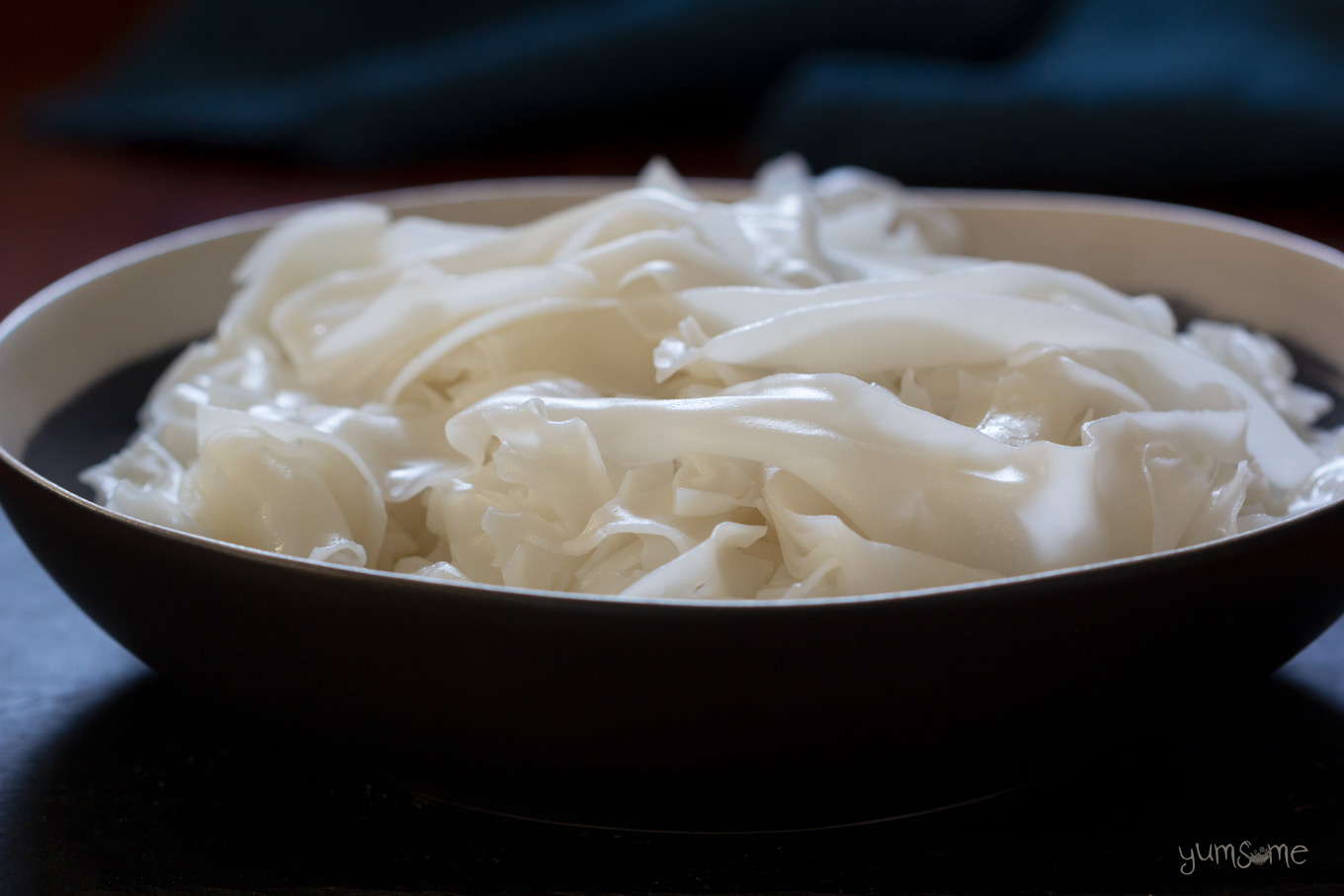 A black dish of cooked sen yai rice noodles.
