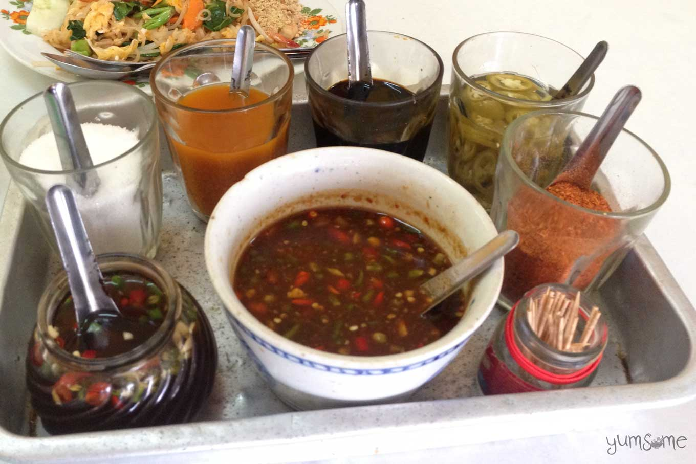 Various Thai condiments on a silver tray.