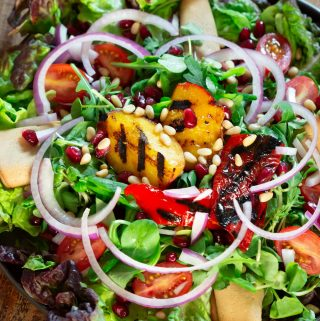 A colourful plate of grilled nectarine salad on a wooden table.
