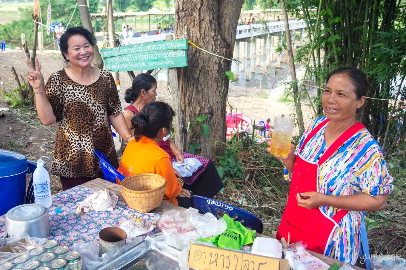 Several Thai women at a trestle table with some cans of drink.