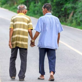 Two Thai men walking along a road, holding hands.