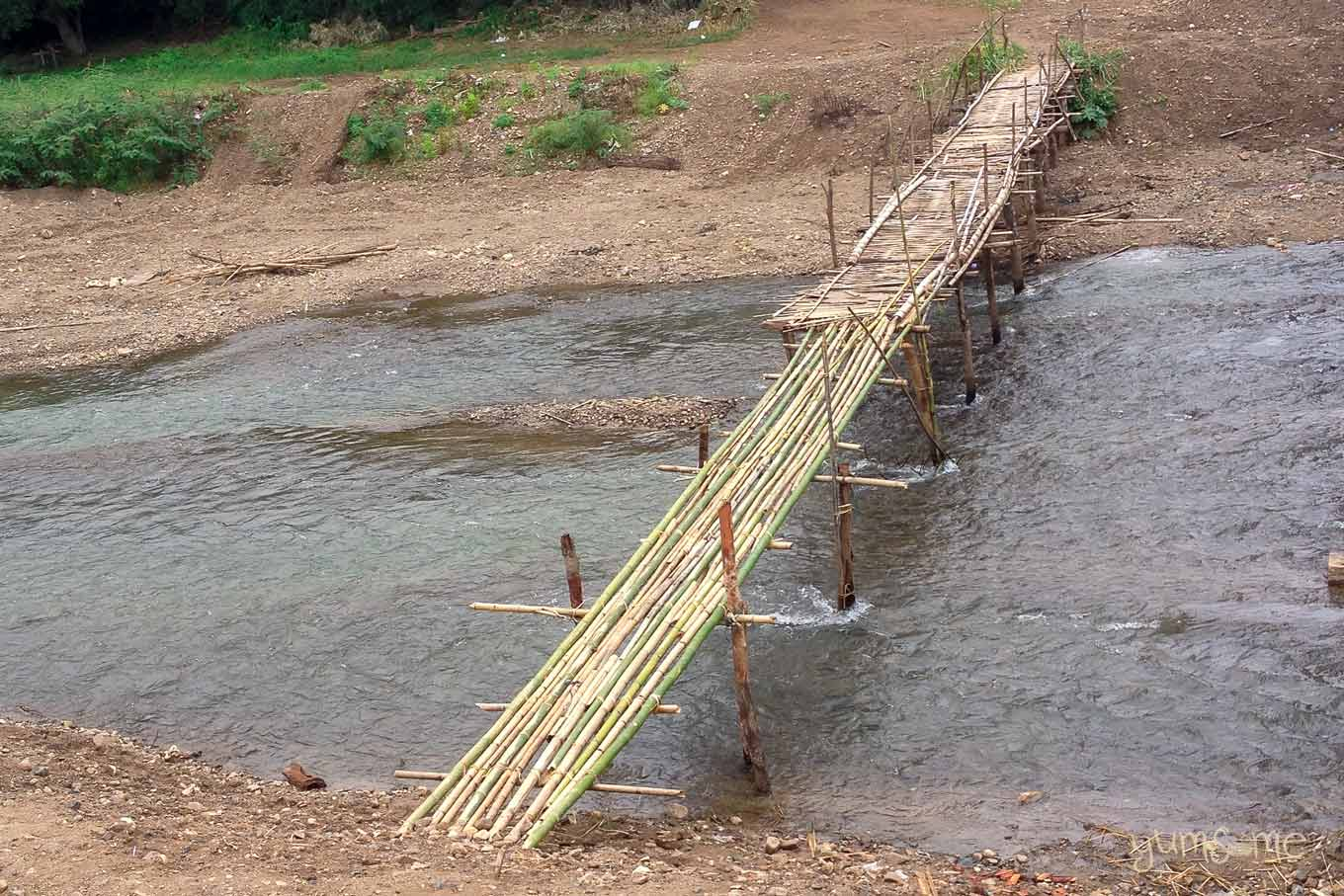 A bamboo bridge spanning a river.