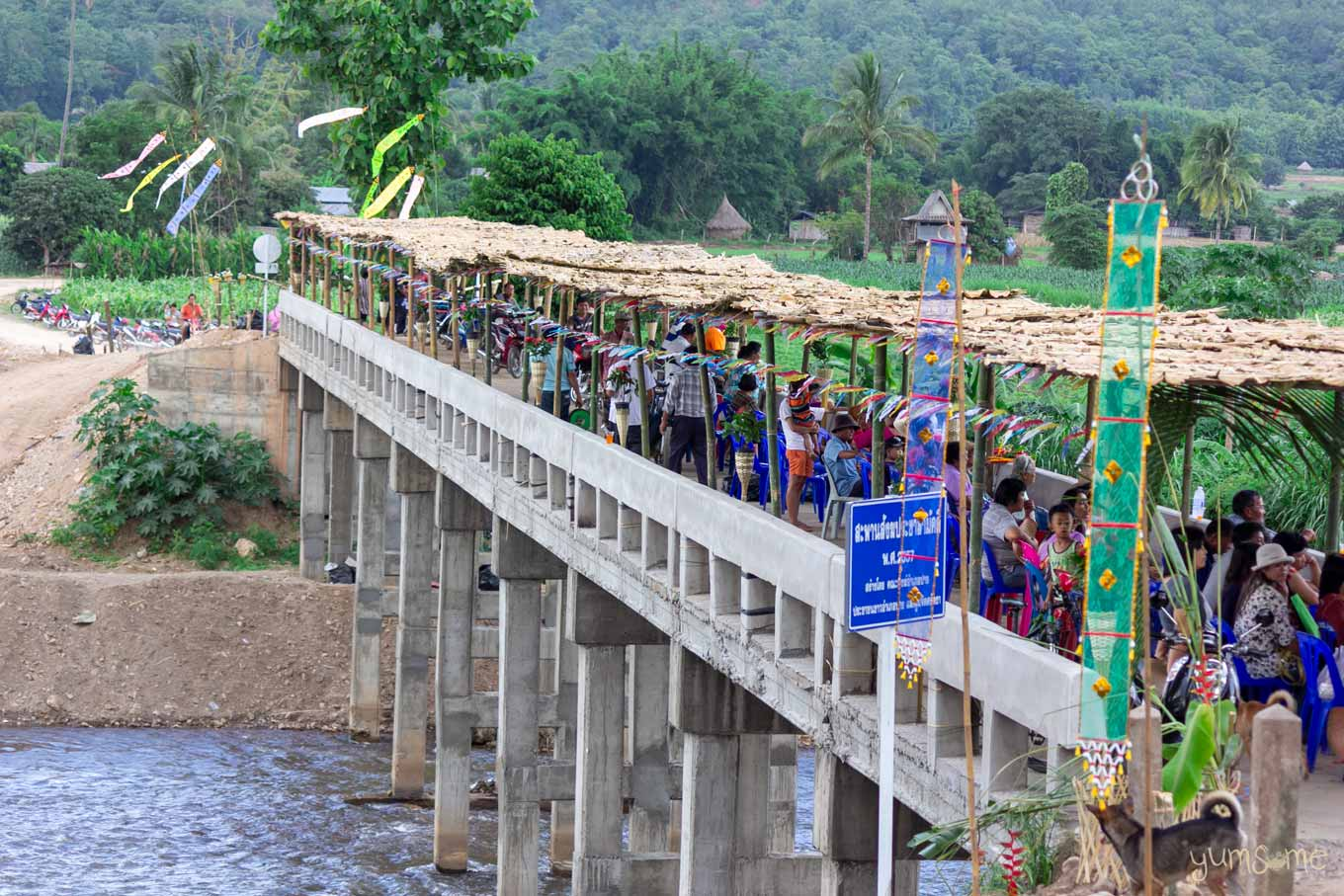 Concrete bridge over a river, with lots of floral and bamboo decoration.