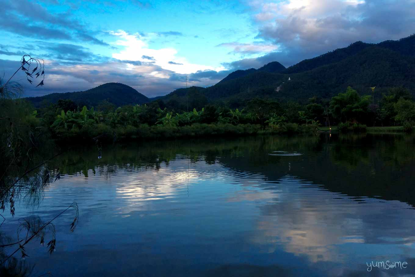 Sunrise over the lake at Bueng Pai Farm, with trees and mountains in the distance.