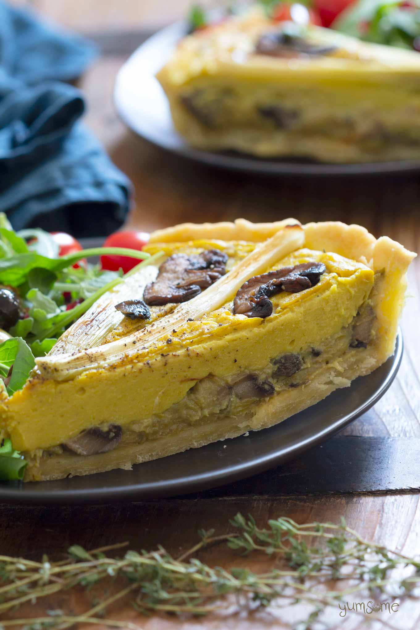 A wedge of mushroom and leek quiche on a black plate.