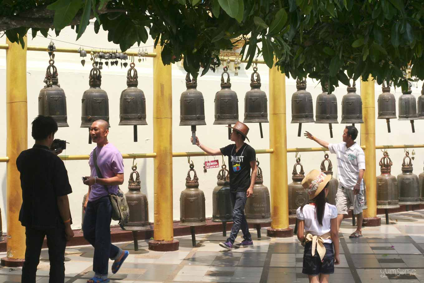 A row of temple bells, with people ringing them, at Wat Doi Suthep.