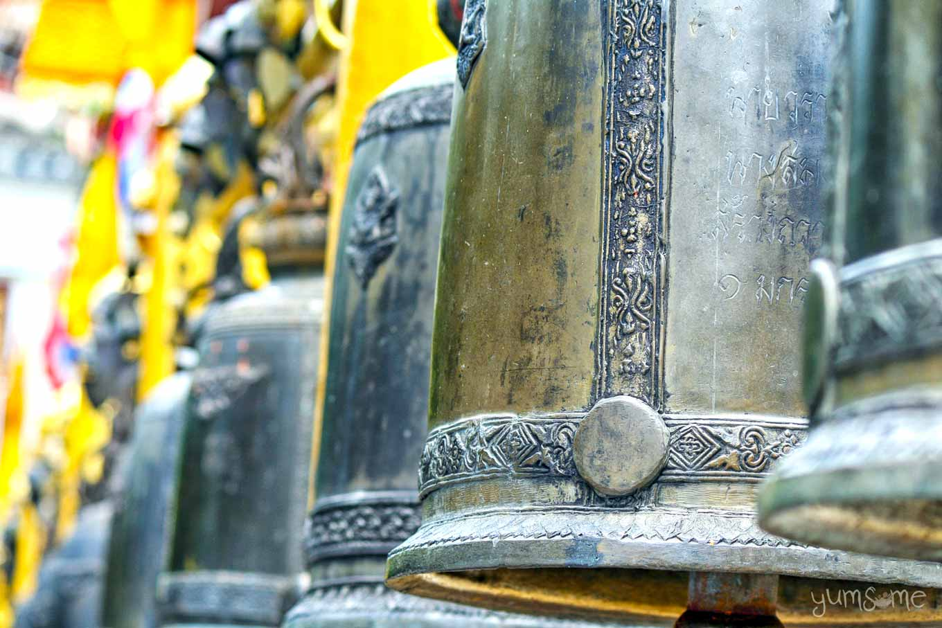 Closeup of some of the temple bells at Wat Doi Suthep, showing an inscription on one of them.