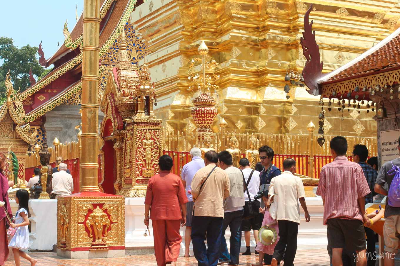 The base of the chedi at Wat Doi Suthep, with people milling around.