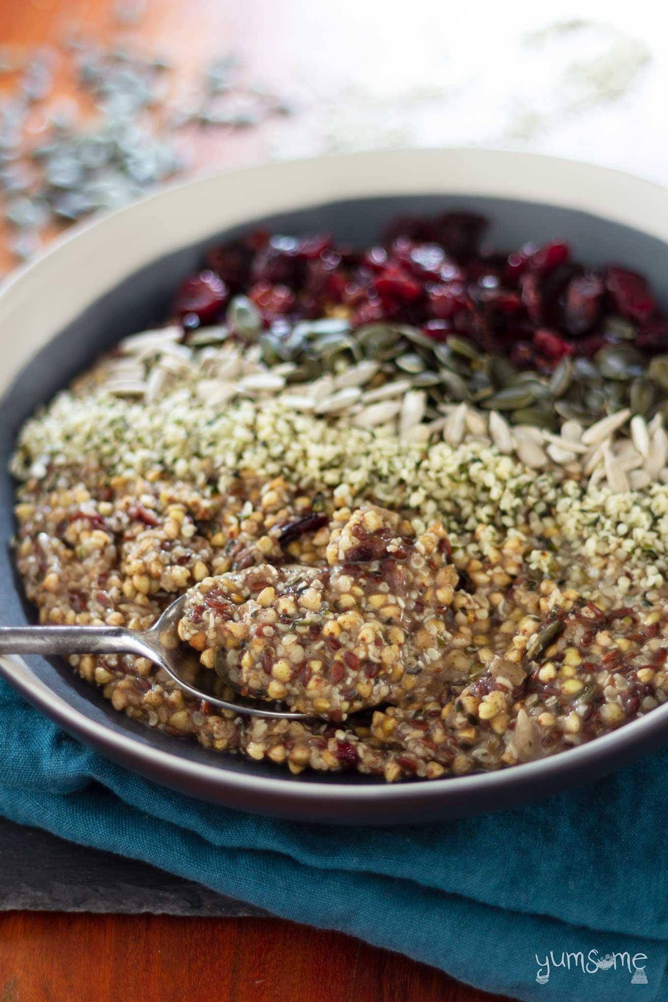 A shot of a bowl of vegan fruity hemp and buckwheat porridge on a blue napkin on a wooden table.