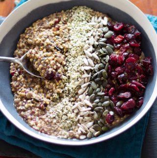 Vegan fruity buckwheat and hemp porridge in a black bowl on a blue napkin.