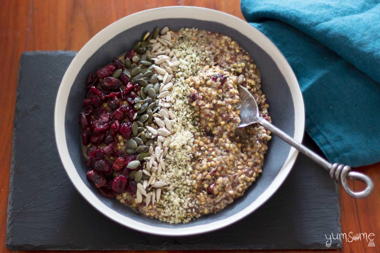A spoon in a bowl of vegan fruity hemp and buckwheat porridge on a black slate, with a blue napkin.