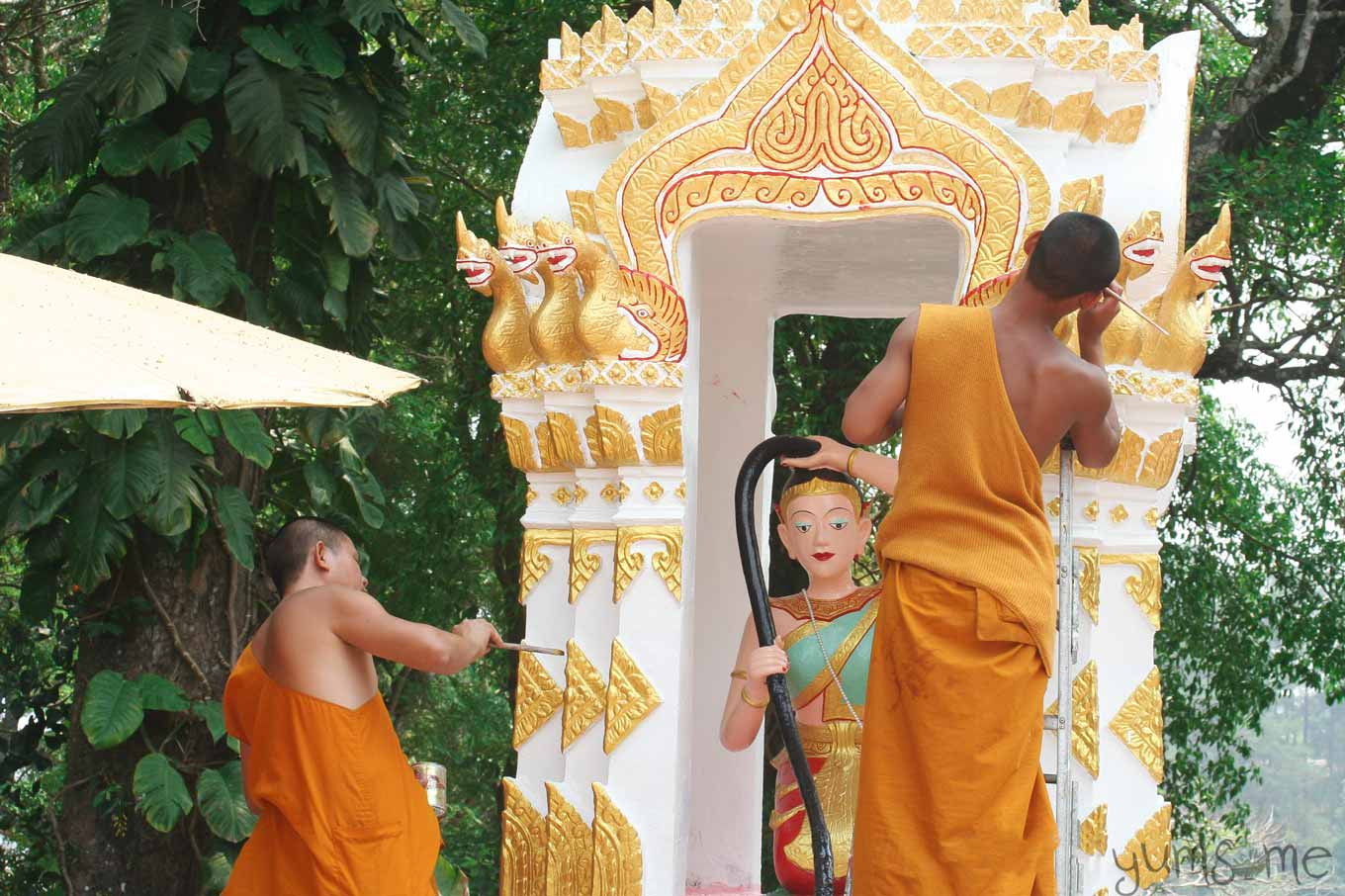 Two Buddhist monks in saffron robes, painting a monument dedicated to the Earth deity, Phra Mae Thorani.