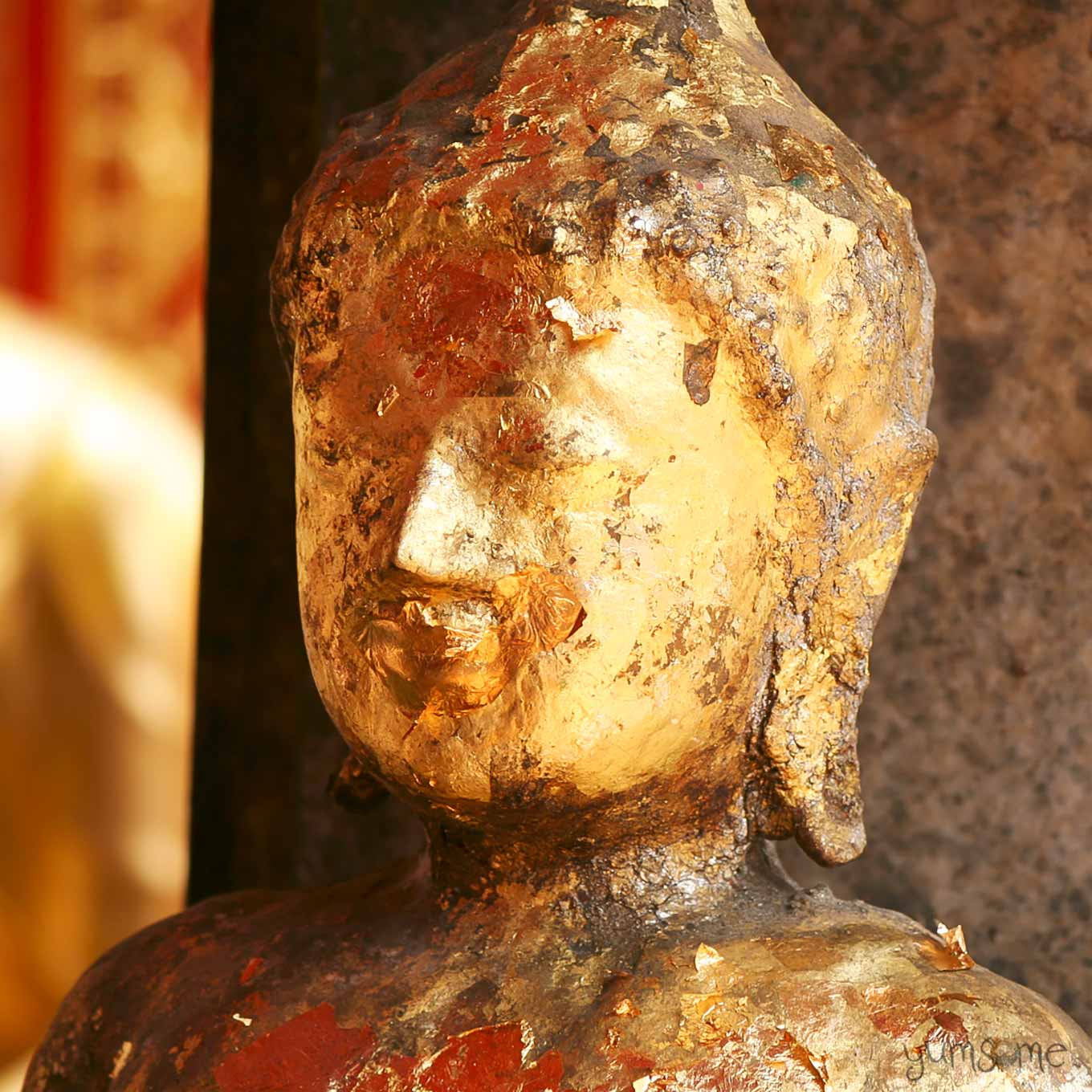An old golden Buddha statue, with flaking gold leaf, showing signs of repeated repair.