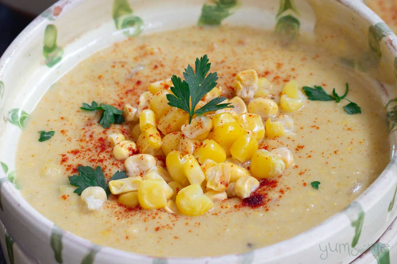 A bowl of vegan sweetcorn chowder with a pile of sweetcorn on top, and garnished with parsley.