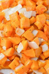 Cubes of roasted butternut squash and piece of onion.