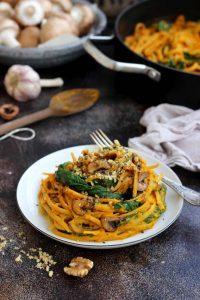 A white plate of spaghetti in pumpkin sauce, against a dark background,