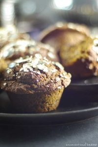 A black plate with seed-topped pumpkin molasses muffins.