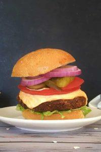 Loaded black bean burger against a dark background.