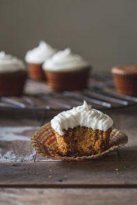Half a vegan pumpkin cupcake on a dark wooden table.